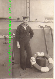 WWII Japanese Navy Sailor Standing next to a life ring on a ship Photo